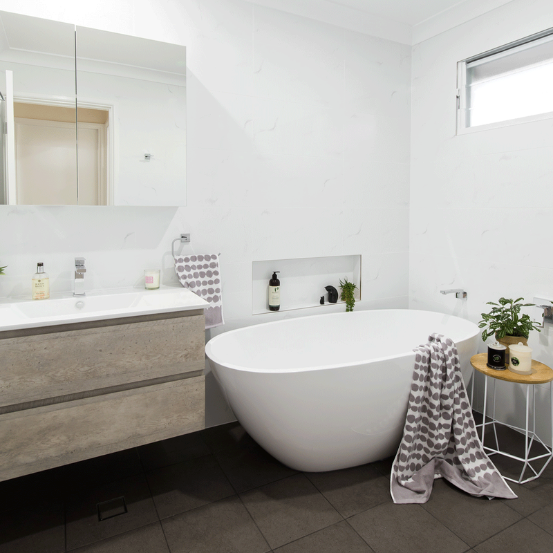 Grey and white bathroom renovation in Alstonville NSW with white free standing tub.
