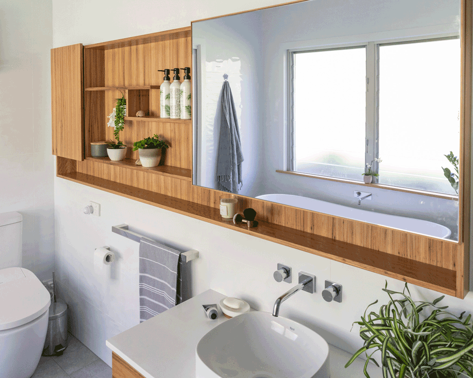 bathroom renovation in Lismore NSW by Northern Rivers Bathroom Renovations featuring blackbutt mirror cabinet with shelves and sliding mirror door and blackbutt wall hung vanity.