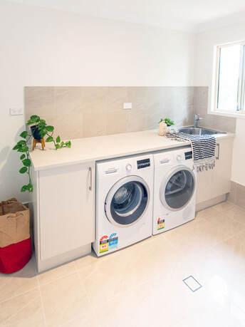 Laundry Renovation with beige coloured bench and cabinets and side by side, under bench washing machine and dryer.